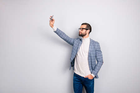 Virile, harsh, education, attractive man in jacket shooting self picture on smart phone front camera, holding hand in pocket of pants, standing over gray background Stok Fotoğraf - 105622714