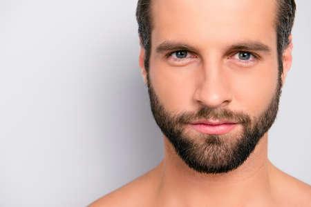 Schließen Sie herauf abgeschnittenes Porträt mit Kopienraum des männlichen, harten, männlichen, attraktiven, nackten, unrasierten, gutaussehenden, atemberaubenden Mannes mit idealer, perfekter Gesichtshaut, Kamera betrachtend, isoliert auf grauem Hintergrund Standard-Bild