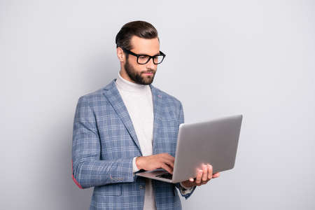 Portrait of half turned, virile, harsh, attractive, intelligent, stunning man in glasses having laptop in hands, checking email, using wifi internet, standing over gray background