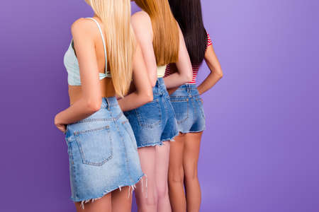 Rear view portrait of different girls with long hair wearing jeans wear isolated on bright violet background. Cellulite varicose treatment concept
