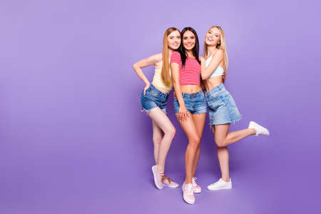 Full body portrait of slender charming girls in casual outfits having thin long legs enjoying free time together isolated on vivid violet background