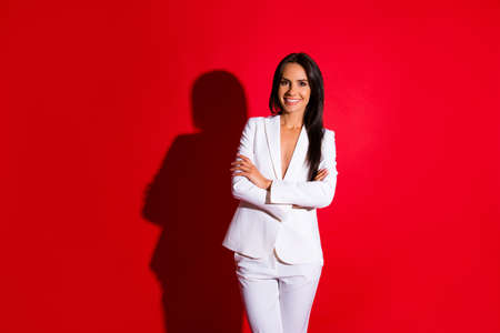 Portrait of cheerful positive woman in white suit holding arms crossed having beaming smile long hair looking at camera isolated on bright red background Фото со стока