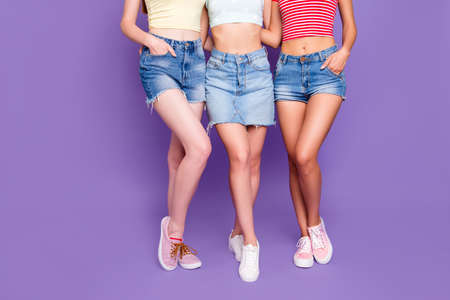 Hair removal waxed beauty wellness wellbeing concept. Cropped portrait of lesbian trio embracing demonstrate smooth ideal skin of legs isolated on bright violet background Zdjęcie Seryjne