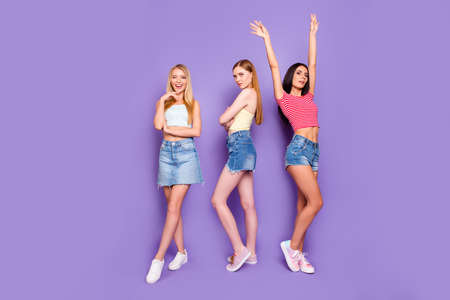 Portrait of professional slender models standing in different pose isolated on bright violet background 스톡 콘텐츠