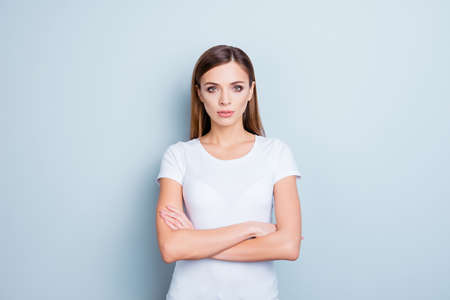 Portrait of perfect cute girl in white t-shirt having holding arms crossed isolated on grey background looking at camera
