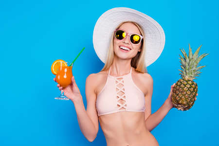 Portrait of funky fancy girl holding pineapple and cocktail with straw in hands enjoying sun isolated on vivid blue background. Girlish pink glamour exotic concept