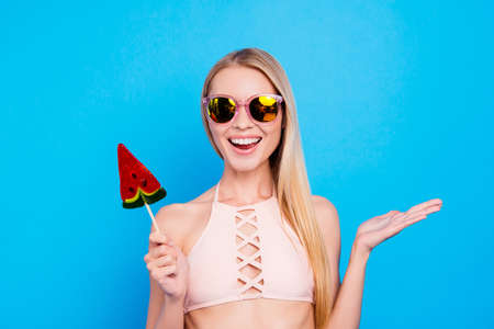 Portrait of cheerful positive girl in eyeglasses with beaming smile gesturing with palm enjoying daydream holding sweet tasty piece of watermelon on stick isolated on vivid blue background