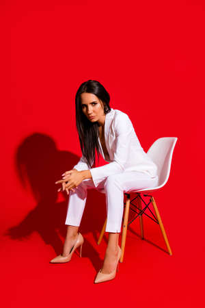Vertical portrait of bad horny woman sitting on stool wearing white outfit looking at camera with angry sight wearing pump shoes isolated on vivid red background
