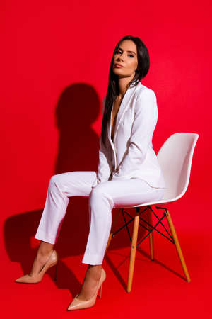 Full size portrait of stunning luxury woman sitting on stool wearing white suit looking at camera isolated on bright red background