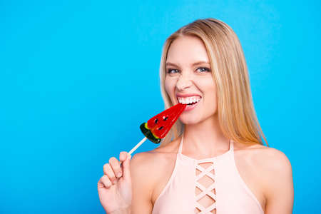 Healthy teeth care toothcare ache treatment concept. Portrait of crazy playful girl biting sweet piece of watermelon on stick isolated on bright blue background
