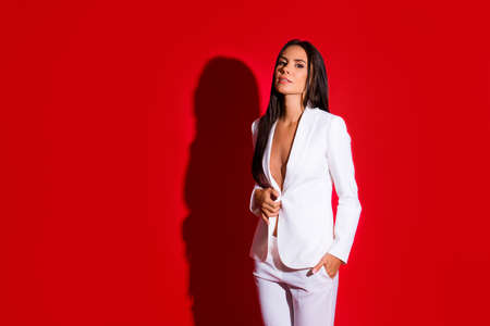 Portrait with copysapce empty place of cool stunning woman in white suit unbutton jacket holding hands in pocket looking at camera isolated on vivid red background. Advertisement concept