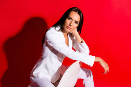 Posing snap portrait of pretty charming woman sitting on chair looking at camera wearing classic white suit isolated on vivid red background