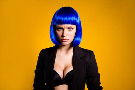 Portrait of stressed depressed woman in vivid blue wig black jacket having big tits looking at camera isolated on yellow background. Relationship life problems troubles concept Stock Photo