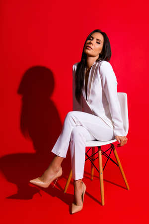 Posing snap portrait of cool hot woman in white suit sitting on chair looking at camera isolated on bright red background. Photoshooting studio concept Archivio Fotografico