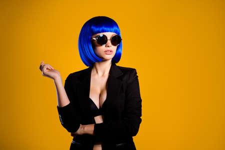 Retrato de mujer traviesa impresionante en chaqueta negra de gafas de verano peluca azul vivo con gran aislado sobre fondo amarillo con sombra Foto de archivo
