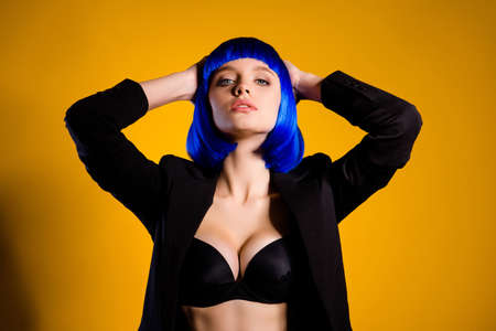 Portrait of hot confident woman with big boobs in black jacket bright blue wig holding hands behind head isolated on yellow background Stock Photo