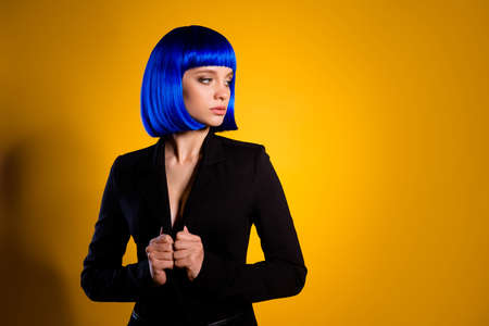 Portrait of tempting seductive girl in classic black jacket bright blue wig looking at empty place copyspace, isolated on yellow background. Advertisement concept