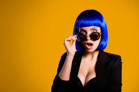 Portrait with copyspace empty place of afraid scared girl looking out glasses with big eyes wide open mouth in bright blue wig isolated on yellow background Stok Fotoğraf