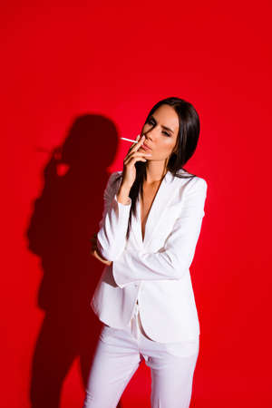 Vertical portrait of stressed disappointed woman smoking cigarette wearing white elegant suit isolated on bright red background Stock fotó