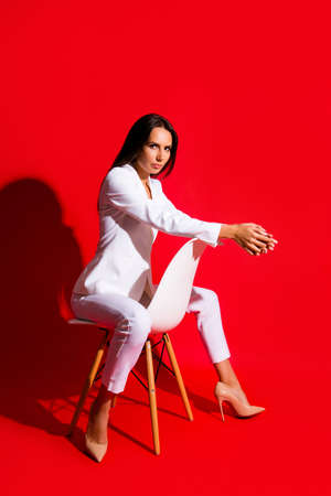 Studio posing snap photoshooting concept. Portrait of stunning cool woman sitting on chair looking at camera isolated on vivid red background