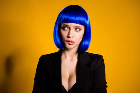 Portrait of worry confused woman in bright blue wig black jacket having sexy decollete big boobs biting low lip looking to the side isolated on yellow background Stock Photo