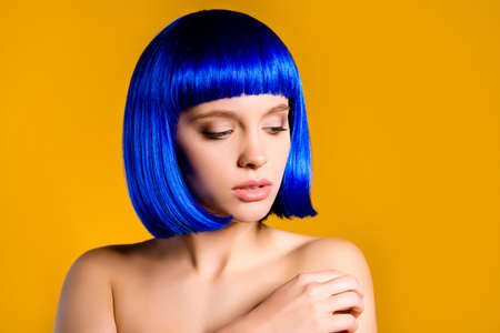 Portrait of sensual attractive woman in blue wig having perfect smooth soft skin isolated on yellow background. Pampering perfection enhancement concept