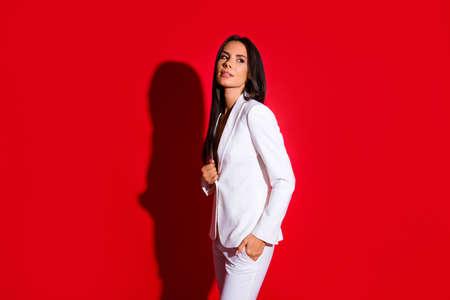Retrato de vista lateral de hermosa mujer encantadora en traje blanco sosteniendo la mano en el bolsillo mirando a otro lado aislado sobre fondo rojo brillante