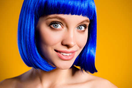 Closeup cropped portrait of cheerful positive lady in blue wig having natural makeup modern hairdo isolated on yellow background looking at camera