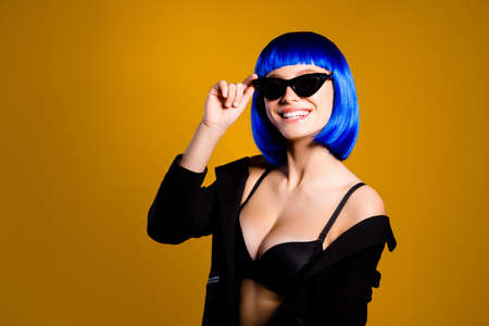 Portrait of positive toothy girl having fun good mood modern eyeglasses big boobs in bright blue wig holding eyelet with hand looking at camera isolated on yellow background Фото со стока