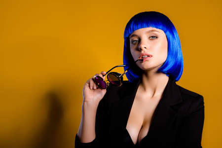 Portrait with copyspace empty place of hottie luxury girl in bright blue wig holding spectacles in hands having big boobs looking at camera isolated on yelow background