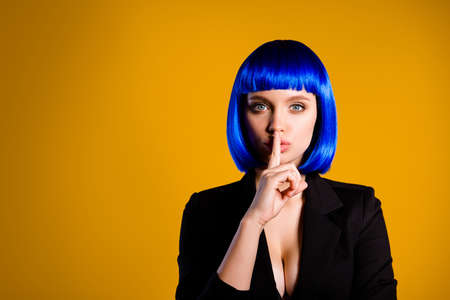 Portrait with copy space empty place for advertisement of mysterious charming girl in vivid blue wig gesturing silence sign with forefinger isolated on yellow background