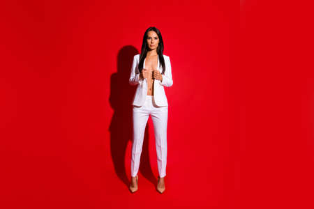 Full body portrait of playful tempting girl taking off jacket looking at camera isolated on bright red background Stock Photo