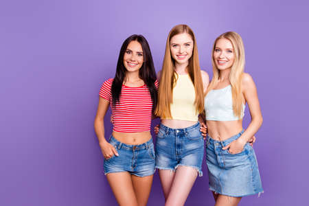 Portrait of charming attractive girls with naked stomach in denim outfits with beaming smiles isolated on bright violet background
