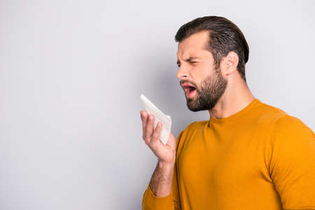 Profile side view half-faced portrait of sad upset unhappy tired ill sick bearded handsome man wearing yellow sweater using paper tissue to blow nose out isolated on gray background copy-space