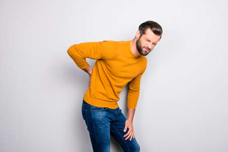Side profile half-turned portrait of grimacing sad upset unhappy with serious pain in back man wearing yellow tight sweater and jeans isolated on gray background copy-space