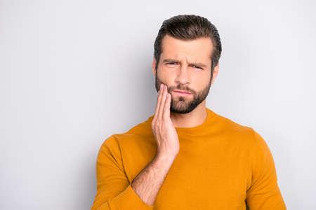 Chiuda sul ritratto dell'uomo barbuto bello turbato infelice nervoso che tocca la sua guancia che ha mal di denti isolato su sfondo grigio