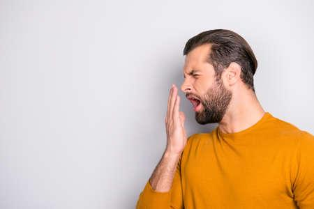 Halbgesichtes Seitenporträt des müden, schläfrigen, gelangweilten, gutaussehenden Bartes, unglücklich mit dem gähnenden Mann der trendigen Frisur, der den Mund mit der Hand isoliert, die auf grauem Hintergrund kopiert wird