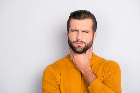 Sore throat influenza concept. Close up portrait of sad unhappy upset ill touching his neck grimacing suffering from pain bearded man isolated on gray background copy-space