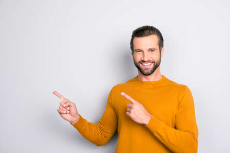 Portrait of cheerful excited expert with idea hairstyle pointing on emphasizing his brilliant idea isolated on gray background copy-space empty blank place Stock Photo