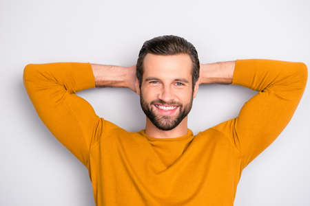 Close up portrait of cheerful excited joyful careless delightful dreamy handsome attractive guy dressed in yellow tight pullover having a rest isolated on gray background Banque d'images