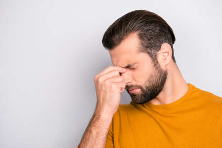 Close up portrait of stressed sick sad upset bearded guy with stylish haircut touching nose-bridge isolated on gray background copy-space Stock Photo