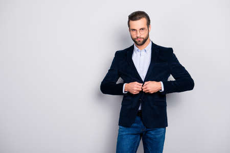 Portrait of handsome serious thoughtful minded graceful modern dreamy elite groomed classy well-dressed classy masculine man fastening velvet dark blue jacket isolated on gray background copy-space