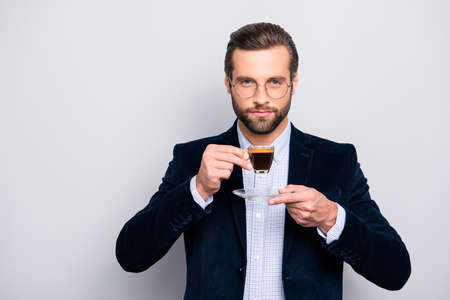 Portrait of chic handsome pleased delightful serious attractive dreamy wealthy elegant classy man smelling the aroma of fresh bitter coffee isolated on gray background copy-space Banco de Imagens - 105622381