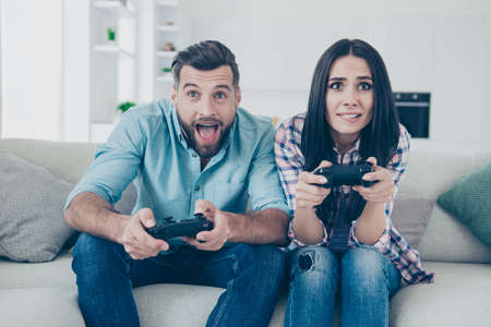 Portrait of funny comic couple holding joy sticks in hands playing video game enjoying activity sitting on sofa indoors