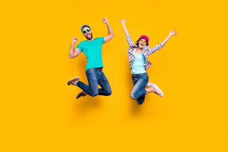 Portrait of lucky successful couple jumping with raised fists celebrating victory wearing denim outfit isolated on bright yellow background.