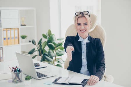 Portrait of charming cheerful financier with beaming smile in classy outfit giving palm front for hand shake sitting in modern workstation