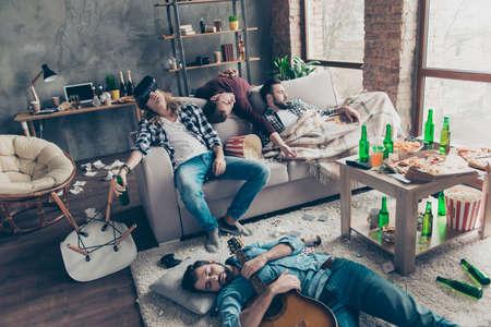 Bärtige, erschöpfte, müde, betrunkene Männer schlafen nach nächtlichen Ereignissen auf dem Boden und dem Sofa in verschiedenen Posen im Wohnzimmer und haben viel Müll, Müll und Müll um sich