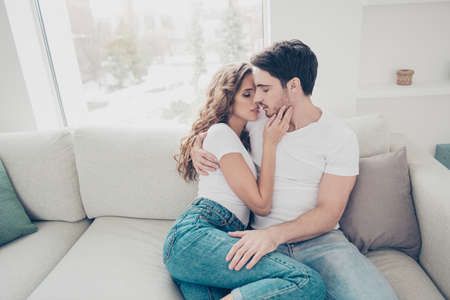 Portrait of sexy romantic couple in casual denim clothes cuddling sitting on sofa indoor kissing with close eyes. Touch gentle satisfaction love story concept Reklamní fotografie