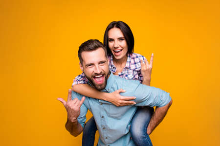 Portrait of funky crazy couple gesturing rock and roll sign yelling, handsome man carrying on back pretty woman looking at camera isolated on vivid yellow background