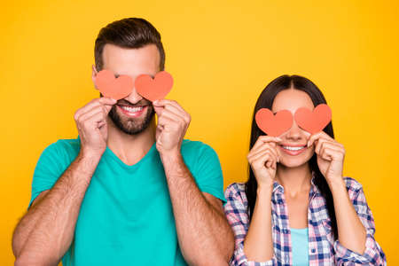 Portrait of creative joyful couple closing eyes with small paper carton red hearts isolated on vivid yellow background. Fall in love story true feelings concept